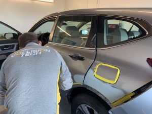 grey car being worked on in a garage